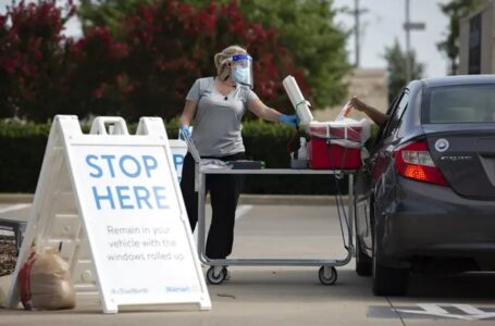 Pharmacist Emily Smith opens a cooler for a patient to place their self-swab coronavirus test at a Walmart drive-thru testing site in McKinney on June 29. Photo credit: Shelby Tauber for The Texas Tribune
